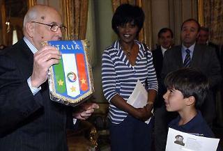 """Il Presidente Giorgio Napolitano mostra il Gagliardetto della Nazionale di Calcio, nel corso di un incontro con gli alunni della scuola elementare """"Ambrit"""" di Roma."""